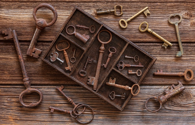 Ancient keys in a wooden box on a vintage wooden background.