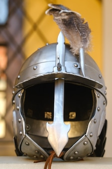 An ancient knight's helmet with a feather .medieval concept. Premium Photo