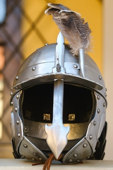 An ancient knight's helmet with a feather .medieval concept.