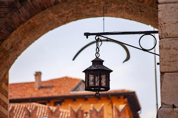 Древний фонарь на средневековых зданиях на улице вероны в италии