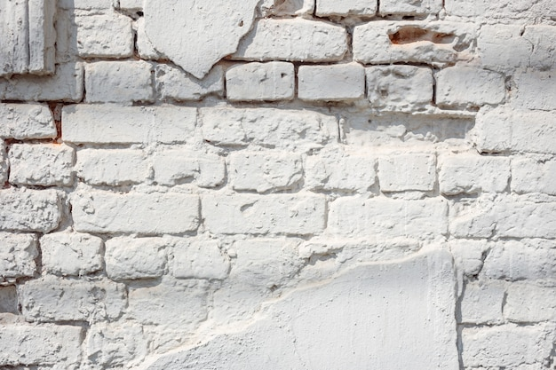Ancient light blue brick wall with peeling plaster. texture or background.