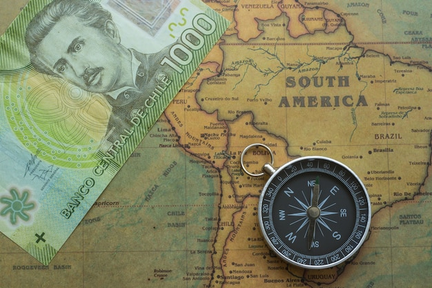 Ancient map of south america with chilean money and a compass,