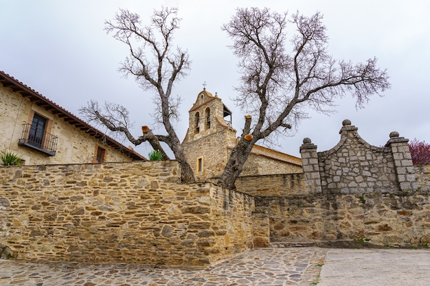 Ancient medieval church made of stone, seen among the trees with bare branches. madrid.