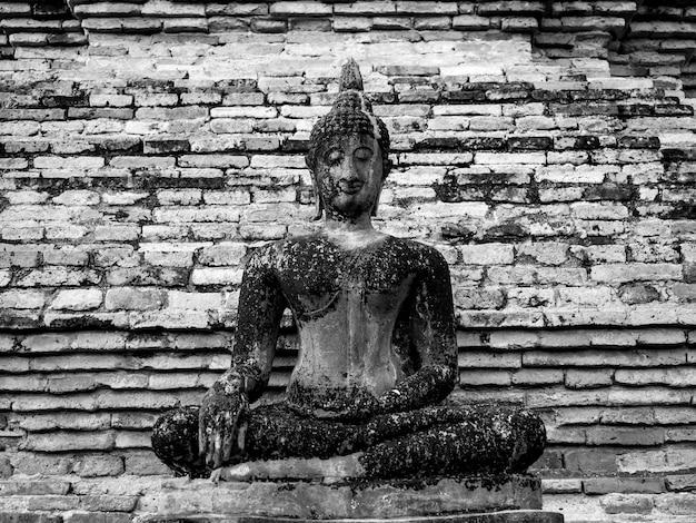 タイのユネスコ世界遺産であるスコータイ歴史公園の境内にあるワットマハタート寺院の古いレンガの壁の背景にある古代の瞑想仏像、黒と白のスタイル。