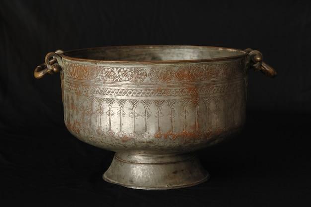 暗い背景に古代の金属製のボウル。アンティークブロンズ食器