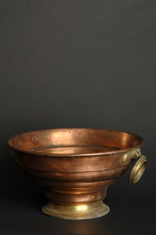 Древняя металлическая чаша на темном фоне. антикварная бронзовая посуда