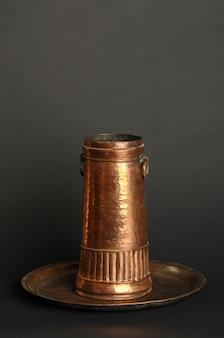 暗い背景に古代の金属のゴブレット。アンティークブロンズ食器