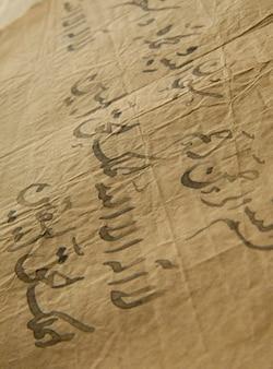 アラビア語の古代の開いた本。古いアラビア語の写本とテキスト