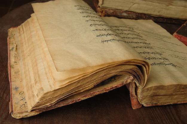 アラビア語の古代の開いた本。古いアラビア語写本