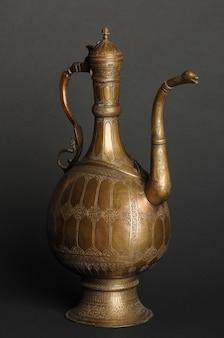 暗い背景に古代の東洋の金属のティーポット。アンティークブロンズ食器