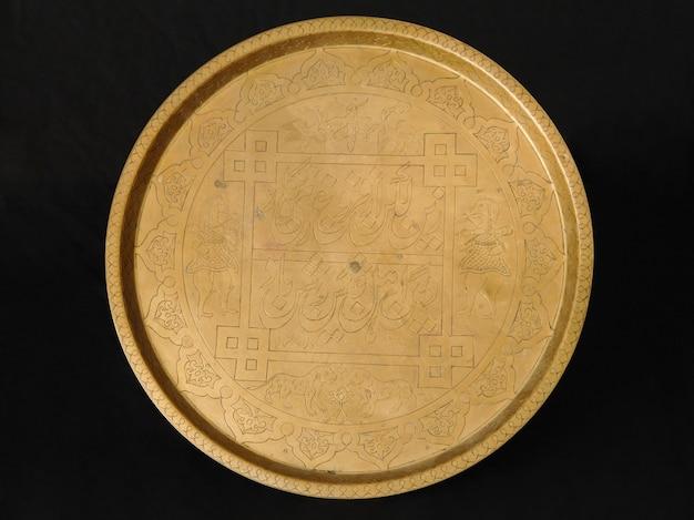 暗い背景の古代オリエンタル金属トレイ。アンティークブロンズ食器