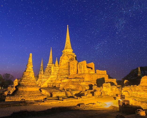 Ancient pagoda at wat phra sri sanphet temple under stars and space dust in the sky