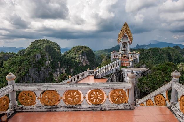Древняя пагода с алтарем на высокой горе возле храма тигриная пещера в провинции краби, таиланд. скалы, покрытые зелеными деревьями и пасмурным небом с дождем на горизонте.