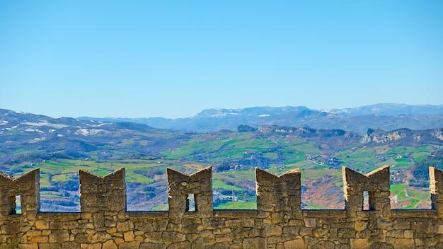 サンマリノの古代のピニオン市壁と背景の山々