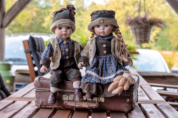 Ancient porcelain dolls sits on suitcase near log farmhouse