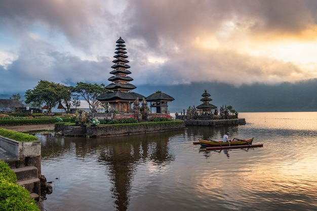 Ancient pura ulun danu bratan temple with tourist paddle and sunrise sky