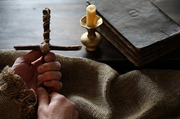 木製と黄麻布の背景に古代の宗教書と木製の十字架
