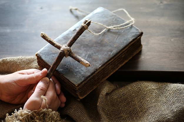 Ancient religious book and wooden cross on the background of a wooden and burlap