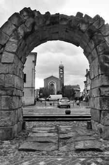 Ancient roman arch in rimini, italy. black and white italian cityscape