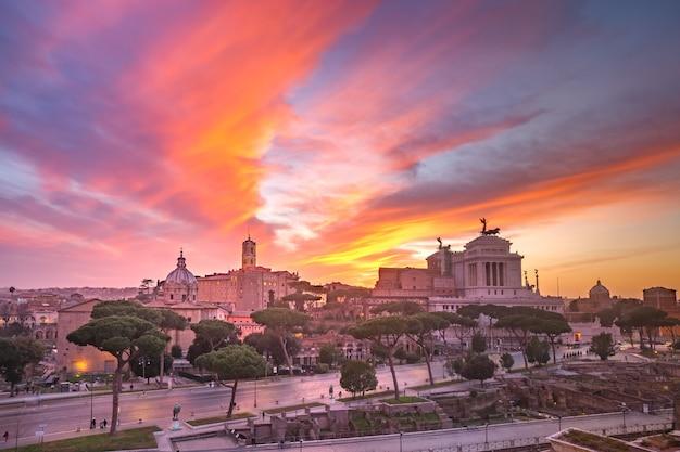 Древние руины римского форума или foro romano и алтаря отечества на восходе солнца в риме, италия.
