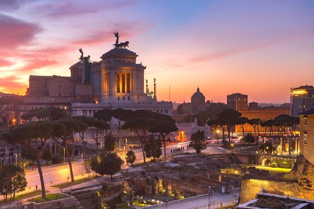 Древние руины форума траяна и алтаря отечества на восходе солнца в риме, италия.