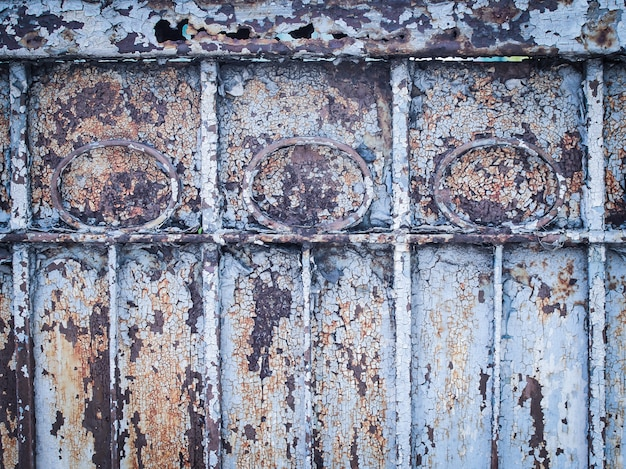 Ancient rust door, scratched blue paint and rust.