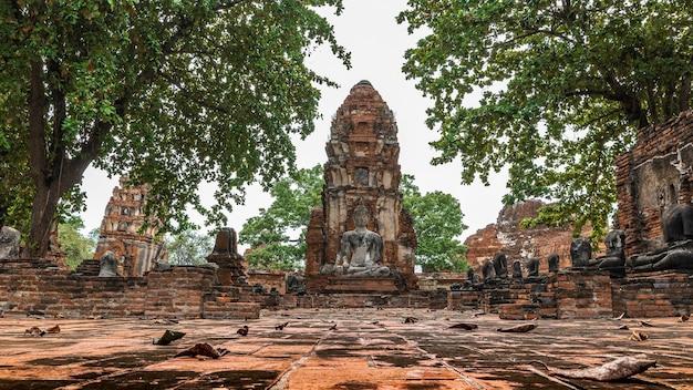 Древняя статуя будды и археологические раскопки в историческом парке ват махатхат аюттхая, провинция аюттхая, таиланд. всемирное наследие юнеско