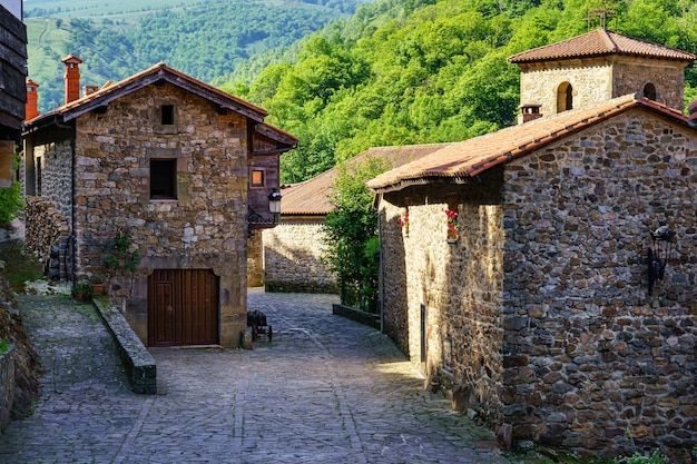 Ancient stone houses and catholic church tower in mountain village