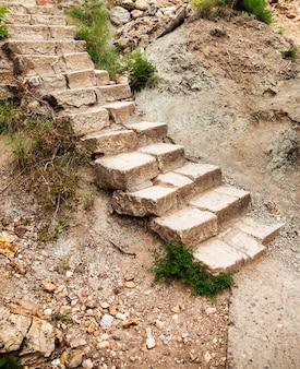 구릉 공원에서 고 대 돌 계단 보도입니다. 산 바위에 이끼가 덮인 계단. 사이트 또는 고해상도 벽지를 위한 아늑한 배경. 여행, 관광 및 모험의 개념입니다. 복사 공간