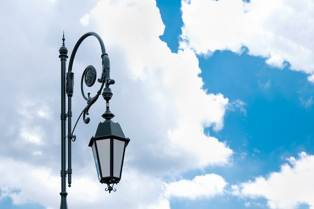 Ancient street lamp against a blue sky with clouds.