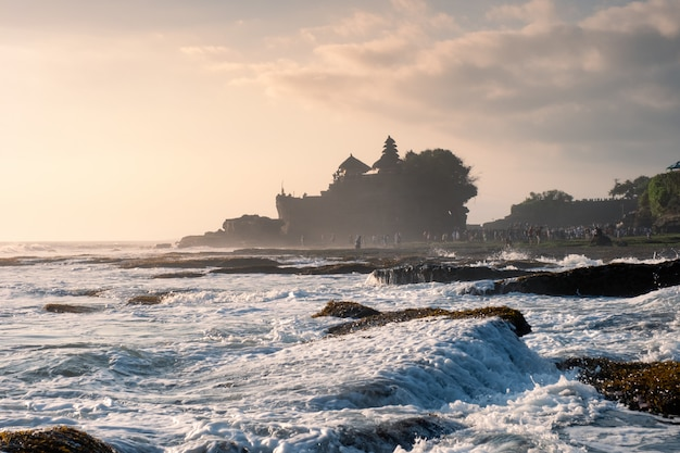 Ancient tanah lot temple on rocky mountain at coastline