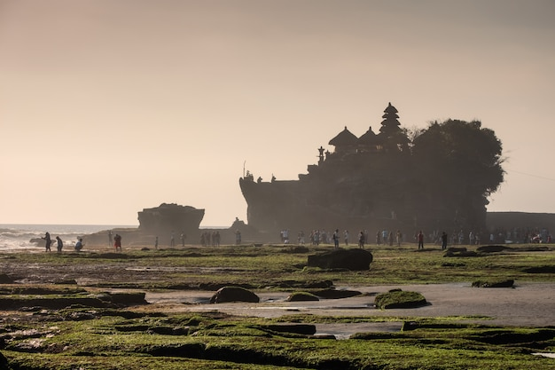Ancient tanah lot temple with dreamy tourists on coastline