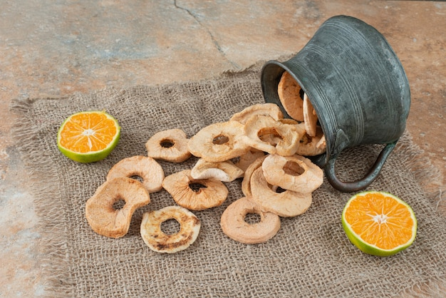 Ancient teapot full of dried apples with half cut tangerine
