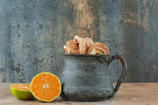 Antica teiera piena di mele secche con mandarino tagliato a metà