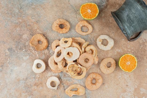 半分カットされたタンジェリンと乾燥したリンゴでいっぱいの古代のティーポット