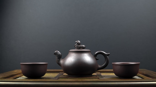 Ancient teapot and two clay bowls on a wooden surface