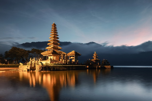 Ancient temple illumination of pura ulun danu bratan with blue sky on the dawn at bali