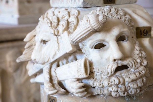 Ancient theatre mask, made of marble, located at the base of a roman column in rome - italy