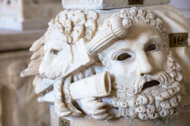 로마의 로마 기둥 기슭에 위치한 대리석으로 만들어진 고대 극장 마스크 - 이탈리아