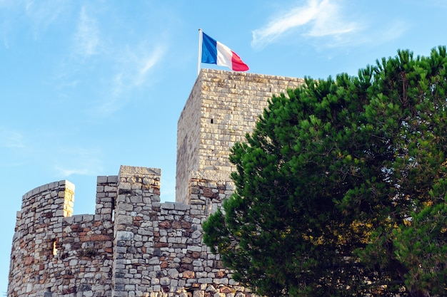 An ancient tower of cannes with the french flag