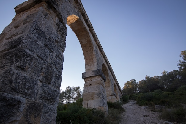 Ancient viaduct bridge from the bottom view in the setting sun
