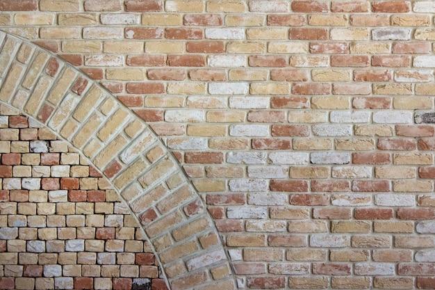 곡선 원이 삽입된 갈색 주황색 벽돌로 만든 고대 벽