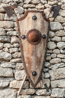 Ancient weapons on a stone wall. wooden shield with iron accents and axes.
