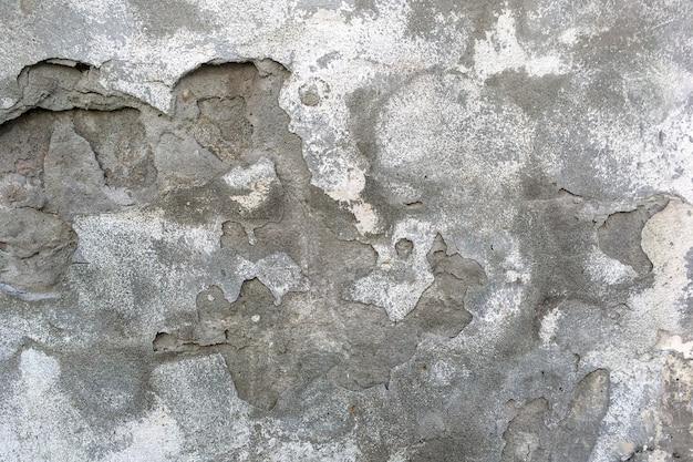灰色の背景の古い建物で古代の風化壁。ひびの入った灰色の剥離石膏。