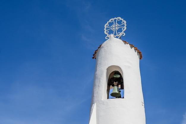 青い空を背景にした古代の白い鐘楼のクローズアップ。ポルトチェルボ、サルデーニャ。コピースペース