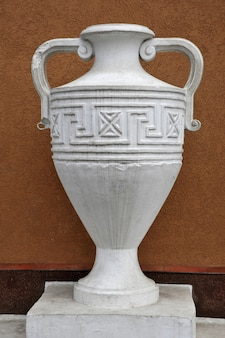 An ancient white stone  vase against the wall.
