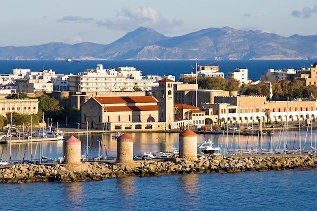 Ancient windmills in rhodes harbor in greece