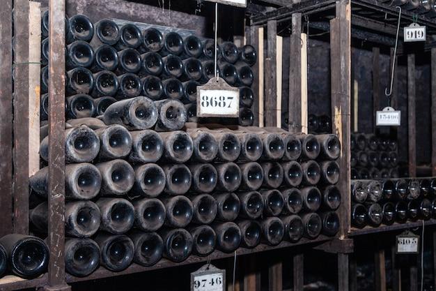 Ancient wine bottles aging in underground cellar in rows