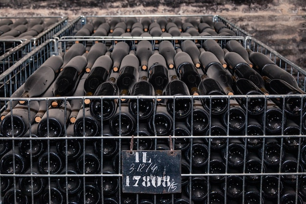 Ancient wine bottles aging in winery cellar in rows