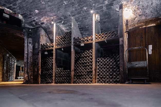 Ancient wine bottles resting, aging, dusting in underground cellar in rows